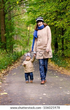 Happy mother with child walking in autumn park
