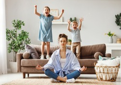 Happy mother with closed eyes meditating in lotus pose on floor trying to save inner harmony while excited children jumping on sofa and screaming in light spacious living room