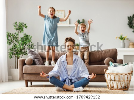 Photo of  Happy mother with closed eyes meditating in lotus pose on floor trying to save inner harmony while excited children jumping on sofa and screaming in light spacious living room
