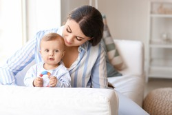 Happy mother with cute little baby at home