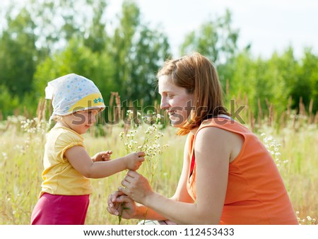 Happy mother with daughter in summer daisy plant