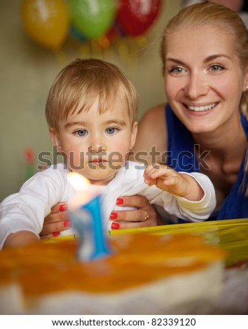 Happy mother with her baby celebrating birthday - stock photo