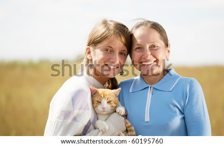Happy mother with her daughter is holding cat against nature