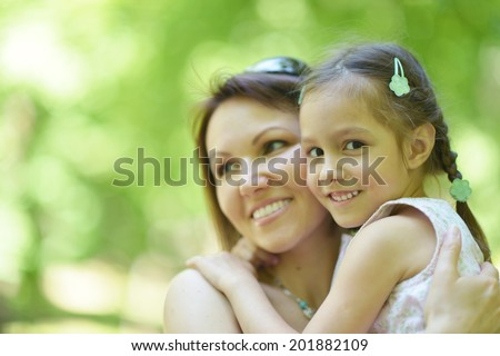 Happy mother with her daughter walk in summer park