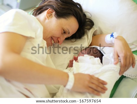 Happy mother with her newborn baby on hospital bed