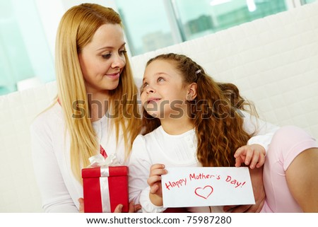 Happy mother with her pretty daughter looking at one another