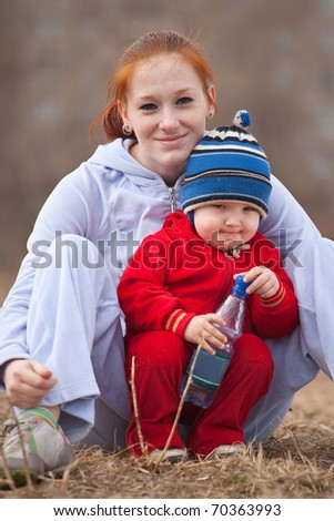 Happy mother with her son  against nature
