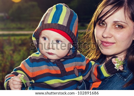 Happy mother with her son in her arms in the park.