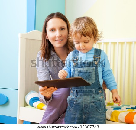 Happy mother with kid and tablet computer in nursery room