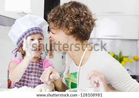 Happy mother with little daughter joyful cooking