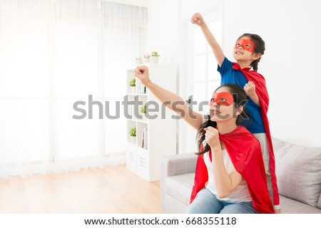 Shutterstock happy mother with little daughter on living room sofa play as superhero together and making same posing ready to fly at holiday leisurely time.