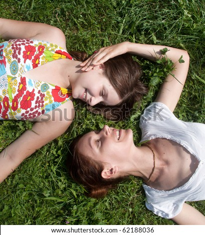 Happy mother with the daughter laying on a grass in park