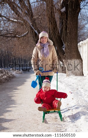 Happy mother with toddler on sled  in winter