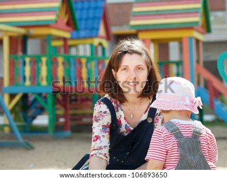 happy mother with  toddler playing  in sandbox
