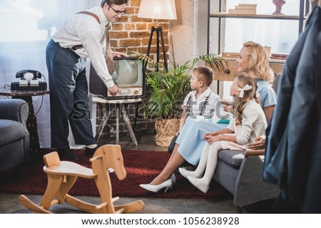 happy mother with two children looking at father turning on vintage tv, 50s style