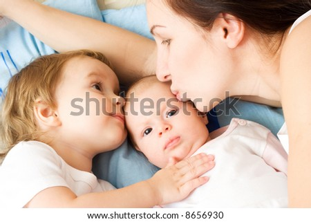 Happy mother with two daughters, kissing and holding them