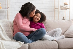 Happy Motherhood. Loving Pregnant Black Mom Kissing Her Little Daughter At Home, Bonding Together While Relaxing On Couch In Living Room, Free Space