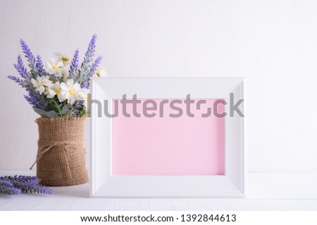 Happy mothers day concept. White picture frame with lovely purple flower in vase on white wooden table.