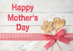 Happy Mothers Day - flower and heart with red ribbon on wooden background