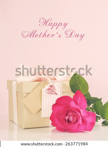 Happy Mothers Day gift of kraft paper gift box with a pink rose, and applied retro vintage style filters and faint light stream.