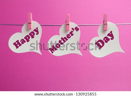 Happy Mothers Day message written across white heart shape gift tags hanging from pegs on a line against a pink background.