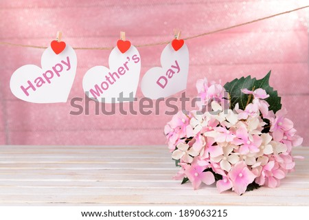Happy Mothers Day message written on paper hearts with flowers on pink background
