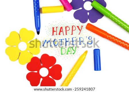 Happy Mothers Day message written on paper with markers and decorative flowers close up