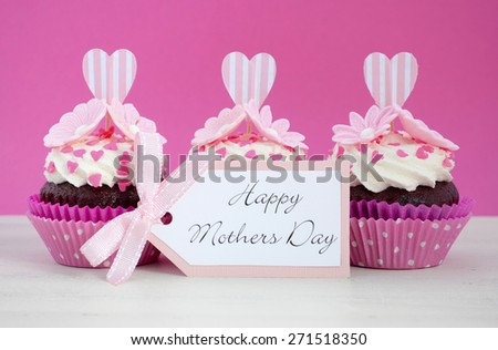 Happy Mothers Day pink and white cupcakes with heart shape topper and hearts and flowers decorations on vintage white wood table.