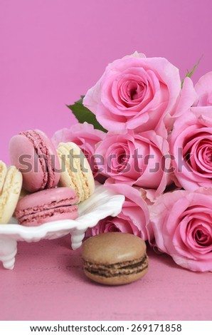 Happy Mothers Day Pink Roses and macarons on vintage style distressed pink wood table.