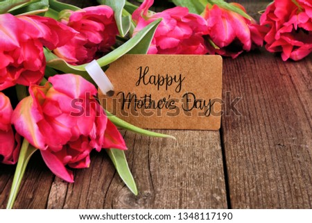 Happy Mothers Day tag close up among a bouquet of pink tulip flowers over a dark wood background #1348117190