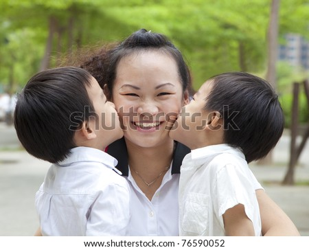 Happy mothers day. two kids kissing mother