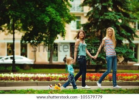 Happy mothers walking together with kid in summer park