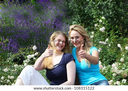 Happy motivated friends giving thumbs up Happy motivated friends sitting close together amongst garden flowers giving thumbs up of approval and hope