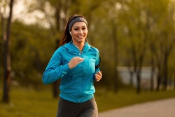 Happy motivated sportswoman running in the park and looking at camera.