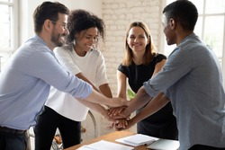 Happy motivated young mixed race diverse colleagues employees joining hands together, showing company staff unity, celebrating professional achievement or successful teamwork, cooperation concept.