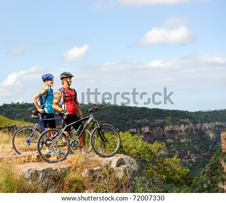 Happy mountainbike couple outdoors have fun together on a summer afternoon - stock photo