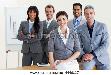 Happy multi-ethnic business people around a conference table smiling at the camera