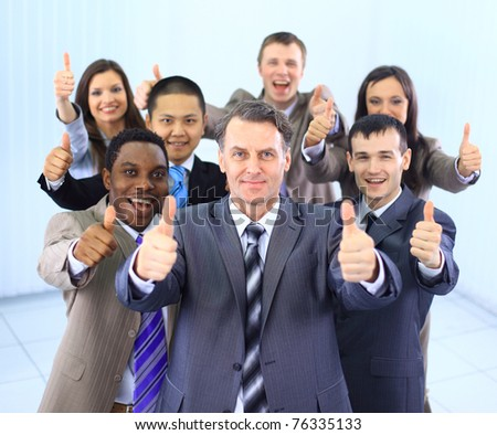 Happy multi-ethnic business team with thumbs up in the office