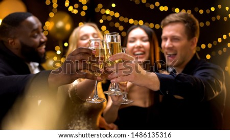 Happy multi-ethnic company clinking beverage glasses, celebrating New Year