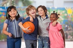 Happy multi ethnic elementary kids playing basketball in school courtyard