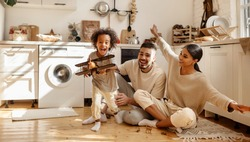 happy multi ethnic family: little boy laughing and playing with   toy airplane in front of his  his parents in the kitchen at home
