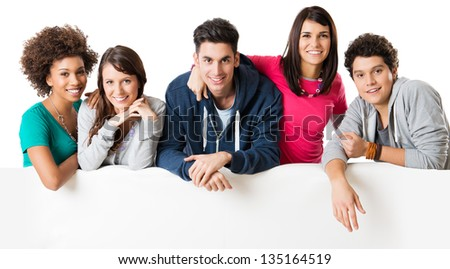 Happy multi ethnic group of friends showing blank billboard isolated on white background