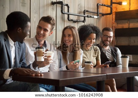 Happy multi ethnic group of friends talking using smartphones in cafe, diverse young people laughing having fun at coffee break in coffeehouse, cheerful millennials enjoying meeting in coffeeshop