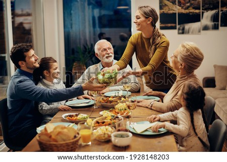 Happy multi-generation family enjoying in a lunch together at home. Focus is on young woman serving salad at dining table.