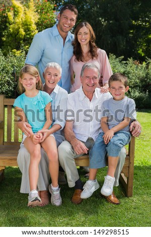 Happy multi generation family sitting in the park on a bench looking at camera
