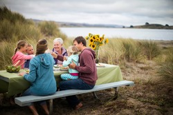 Happy multi-generational family enjoy an outdoor lunch at the beach.
