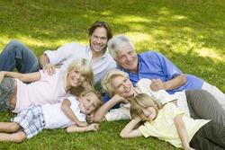 Happy multi-generational family posing in grass