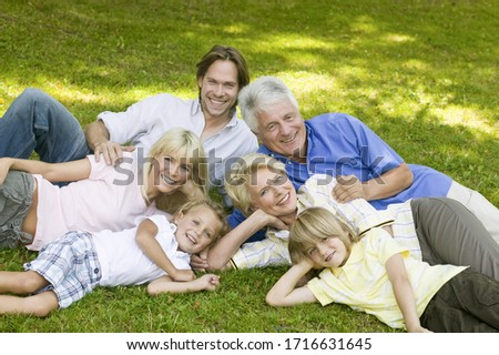 Happy multi-generational family posing in grass