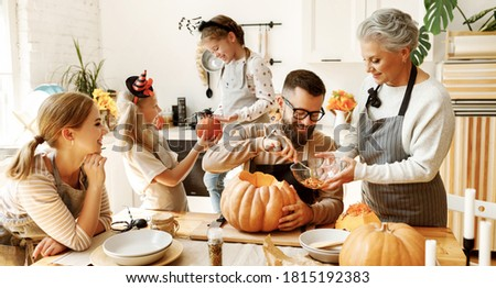 Happy multi generational family smiling and carving jack o lantern from pumpkin while gathering around table during Halloween celebration Foto stock ©