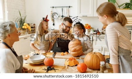 Happy multi generational family smiling and carving jack o lantern from pumpkin while gathering around table during Halloween celebration